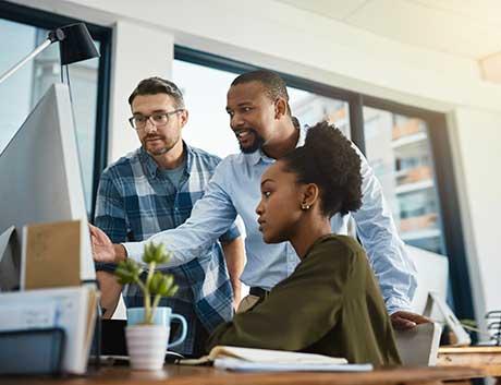 3 colegas a olhar para o monitor de projetos