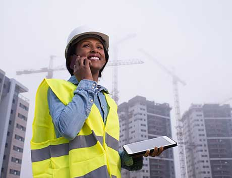 gestora de obras a sorrir e a trabalhar com um software de gestão no tablet