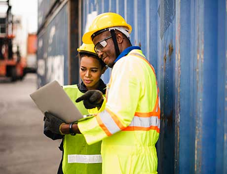 dois colegas de indústria a consultar informação de gestão no portátil