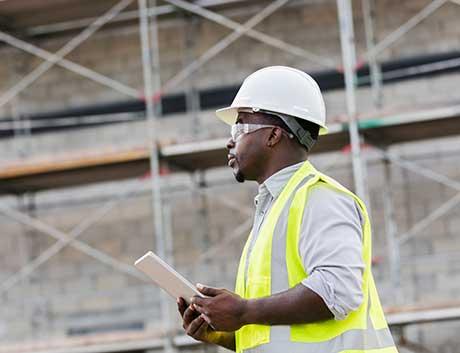 trabalhador de uma obra de construção civil equipado com colete, óculos e capacete
