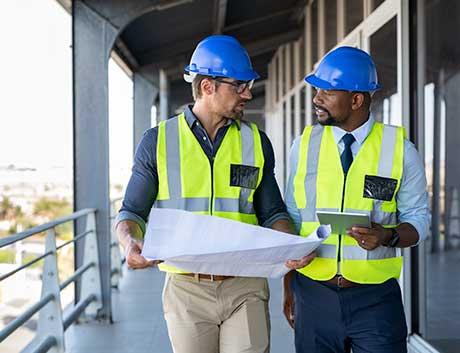 Dois gestores de uma obra de construção civil que recorrem ao programa de gestão PHC CS