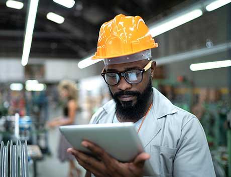 trabalhador de uma fábrica a consultar informação num tablet