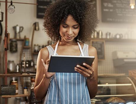 dona de um café a controlar a gestão do seu negócio através de um software no tablet