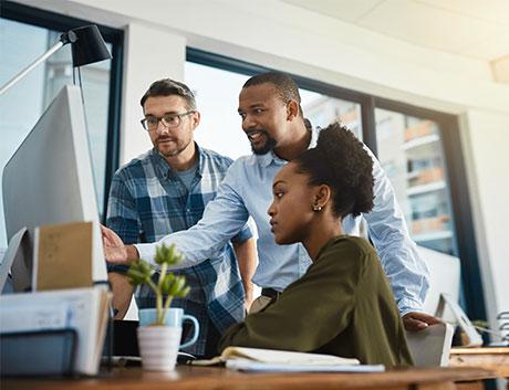 três colegas a olhar para o computador