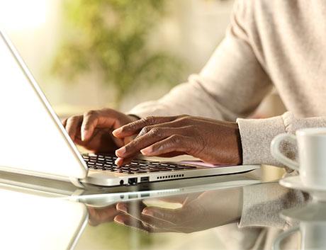 pessoa a escrever no teclado do portátil